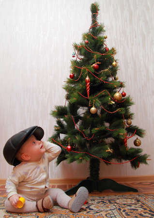 baby in peakes cap near Christmas tree photo