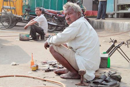 COSTUMERS: Delhi, India - February 18, 2015 repairmen wait costumers on the street in Delhi, India