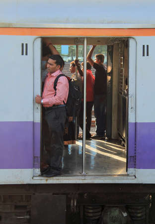 local 27: Mumbai, India - February 27, 2015 people are standing in the moving carriage of local train, Mumbai