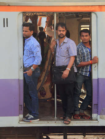 local 27: Mumbai, India - February 27, 2015 people are standing in the moving carriage of local train, Mumbai, India