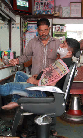 shaving blade: Mumbai, India - February 28, 2015 barber is shaving a man using an open razor blade, Mumbai