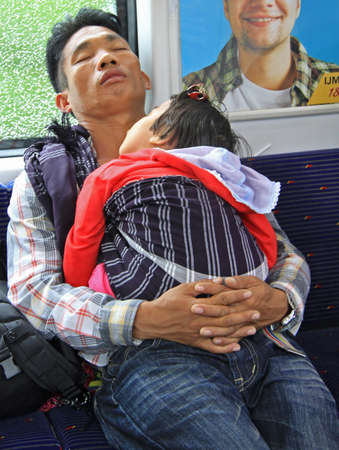 teaching stations: Kuala Lumpur, Malaysia - April 6, 2015 father with baby daughter in carrage of commuter train, Kuala Lumpur