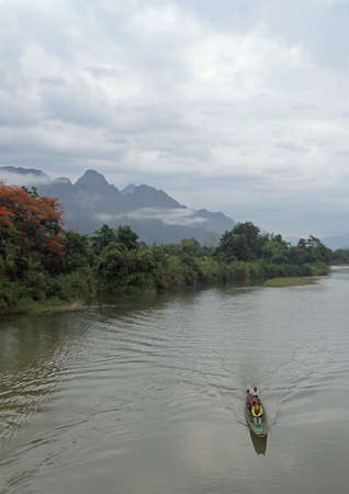 lao: Vang Vieng, Lao - May 17, 2015 tourists are floating in canoe nearly Vang Vieng, Lao Stock Photo