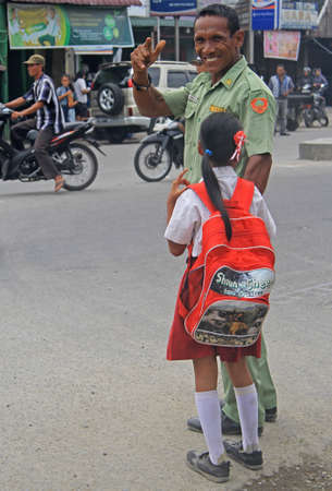 muslim baby girl: Medan, Indonesia - April 15, 2015: police officer with small daughter is smiling and showing welcoming gesture