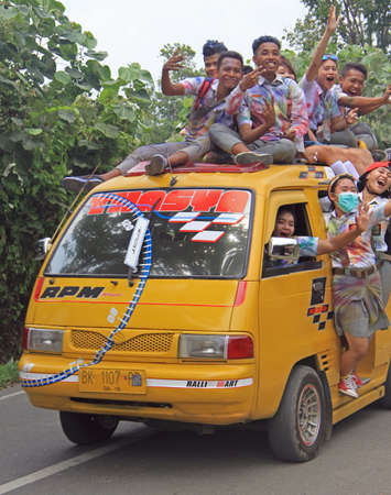 finishing school: Medan, Indonesia - April 15, 2015 students are going to celebrate of finishing of school and moving to tourist place in the van - someone even on the roof of van Editorial