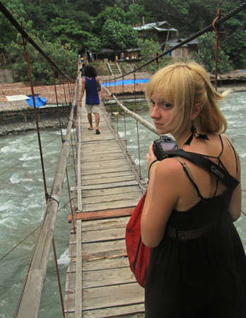 bukit: Bukit Lawang, Indonesia - April 15, 2015: beautiful girl is looking back with fright on the bridge in Bukit Lawang, Indonesia