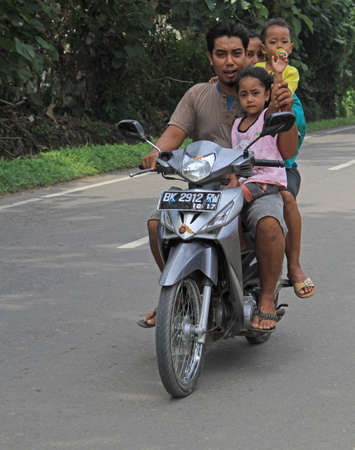 babys dummies: Medan, Indonesia - April 15, 2015: four people are riding on the motorbike in Indonesia