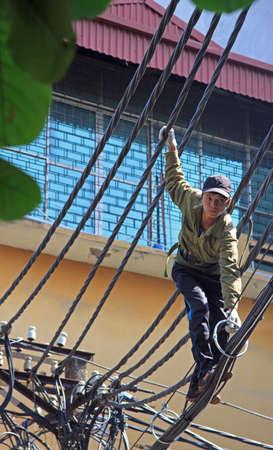 electricidad industrial: Hanoi, Vietnam - 1 de junio de 2015: el hombre está tratando de reparación de cables eléctricos