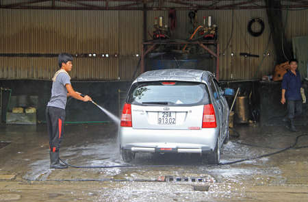 laves: Hanoi, Vietnam - June 2, 2015: serviceman is washing a car