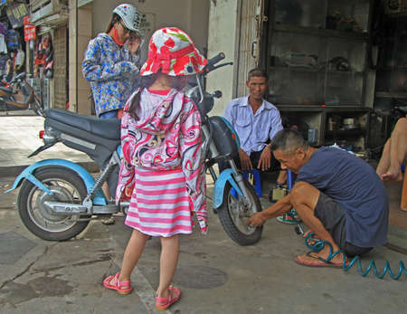 motorcycle repair shop: Hanoi, Vietnam - June 2, 2015: people are waiting while master fill by pumping the tube of scooter