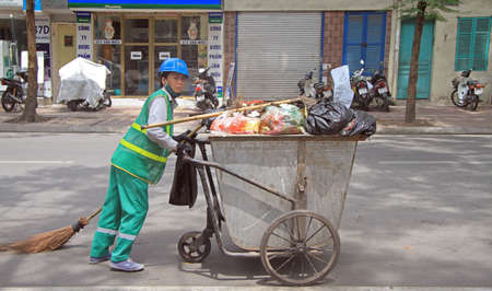 wheeling: Hanoi, Vietnam - June 2, 2015: street cleaner is wheeling trolley with garbage in Hanoi
