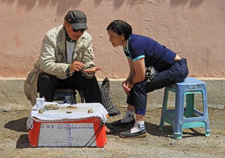 conversating: Ulaanbaatar, Mongolia - July 8, 2015: two street sellers are conversating on the street in Ulaanbaatar