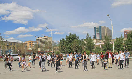 common people: Ulaanbaatar, Mongolia - July 8, 2015: big group of people is repeating common dance on the square in Ulaanbaatar