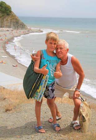grandchild: grandchild and grandpa against the background of the sea beach