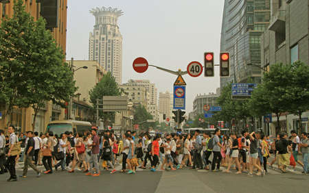 people: Shanghai, China - July 1, 2015: people are crossing road by crosswalk in Shanghai, China
