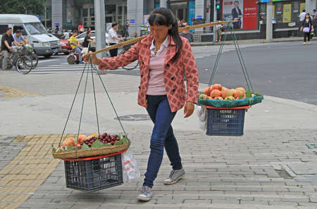 china people: Shanghai, China - July 2, 2015: woman is carrying balancing arm with baskets of fruits in Shanghai