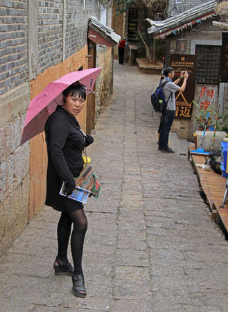 hoer: Lijiang, China - June 10, 2015: woman with pink umbrella is waiting someone on the street in Lijiang, China