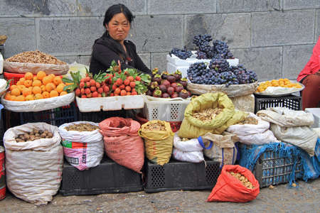 spicery: Lijiang, China - June 10, 2015: woman is selling fruits and spicery on the market in Lijiang, China