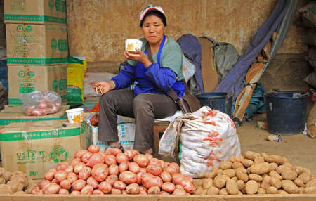 china people: Lijiang, China - June 10, 2015: seller of potato is eating noodle on the market in Lijiang, China