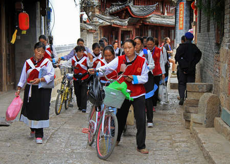 clothed: Lijiang, China - June 10, 2015: big group of women clothed in the same clothes is moving on the street in Lijiang, China