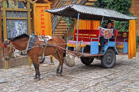 coachman: Lijiang, China - June 11, 2015: coachman of horse-drawn vehicle is waiting customers on the street in Lijiang, China Editorial