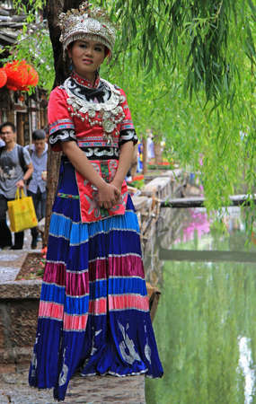 miao: Lijiang, China - June 11, 2015: girl in bright colorful costume is standing on the street in Lijiang, China Editorial