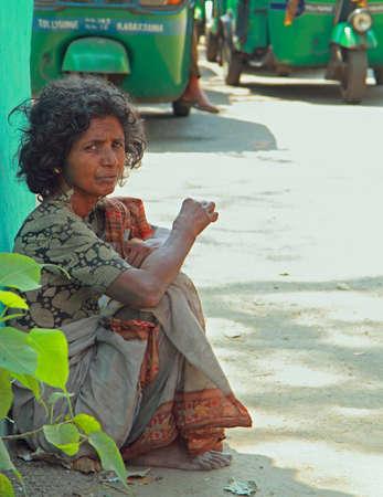 kolkata: Kolkata, India - March 15, 2015: poor woman is sitting on the pavement in Kolkata, India Editorial
