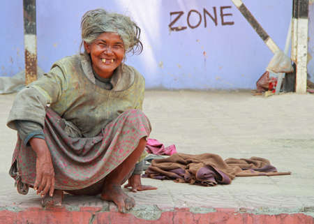 toothless: Kolkata, India - March 15, 2015: old toothless woman is sitting on the pavement on the street in Kolkata