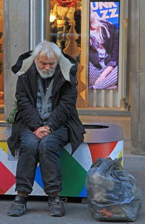warm up: Milan, Italy - November 28, 2015: homeless is trying to warm up on the street in Milan, Italy Editorial