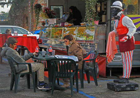 show case: Verona, Italy - 26 November 2015: mom and her son are sitting in cafe on open air