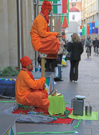 levitation: Milan, Italy - November 27, 2015: Street performers are showing a magical trick, levitation in the air