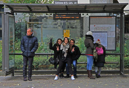 waiting girl: Milan, Italy - November 28, 2015: people are waiting for bus on stop station in Milan Editorial