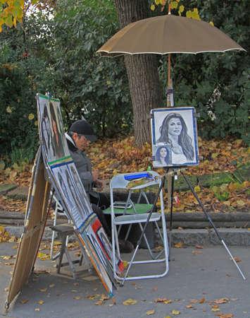 custumer: Milan, Italy - November 29, 2015: street portrait-painter is waiting for new order in Milan