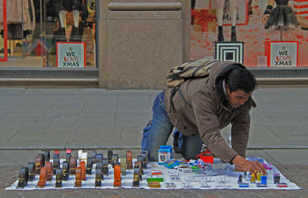illegal immigrant: Milan, Italy - November 29, 2015: street seller is laying out goods in Milan Editorial