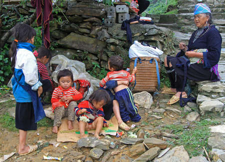barefooted: Sa Pa, Vietnam - June 6, 2015: children and their mother are sitting outdoor in Sa Pa, Vietnam