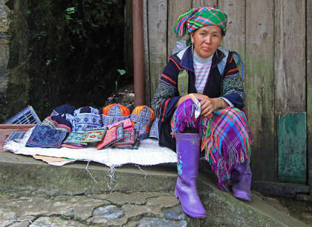 gum boots: Sa Pa, Vietnam - June 6, 2015: woman in traditional clothes is selling accessories Editorial