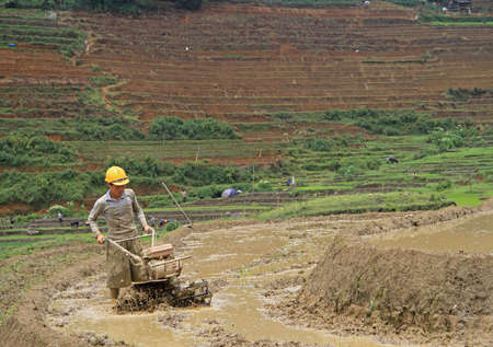cultivator: Sa Pa, Vietnam - June 6, 2015: man is working the soil by manual cultivator in village CatCat, Vietnam