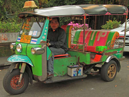 three wheeler: Bangkok, Thailand - March 19, 2015: man is driving tuk-tuk in Bangkok, Thailand