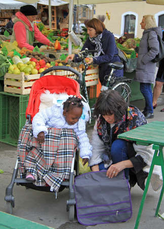 multiracial family: Ljubljana, Slovenia - November 17, 2015: multiracial family is walking on the street market in Ljubljana, Slovenia