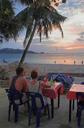 phuket food: couple are watching sunset at the Patong beach, Thailand Stock Photo