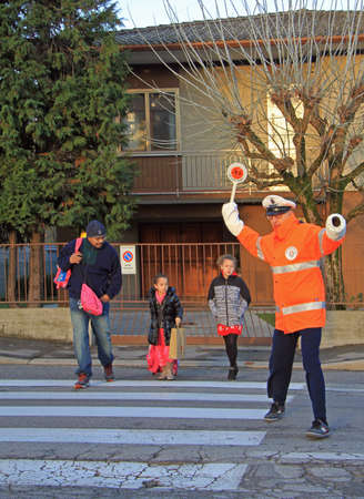 traffic controller: Vicenza, Italy - November 24, 2015: traffic controller is helping to cross a pedestrian crossing in Vicenza, Italy Editorial