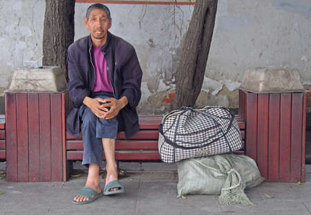 wuhan: Wuhan, China - June 22, 2015: man is resting on a bench outdoor in Wuhan, China