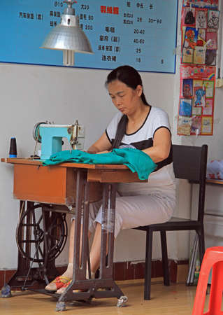 wuhan: Wuhan, China - June 22, 2015: woman is using a sewing machine outdoor in Wuhan, China