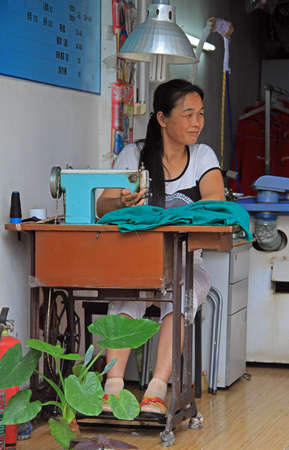 stitching machine: Wuhan, China - June 22, 2015: woman is using a sewing machine outdoor in Wuhan, China