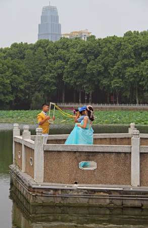 wuhan: Wuhan, China - June 23, 2015: newlyweds are making interesting photos outdoor in Wuhan, China