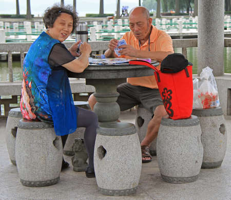 wuhan: Wuhan, China - June 23, 2015: man and woman are playing cards outdoor in Wuhan, China