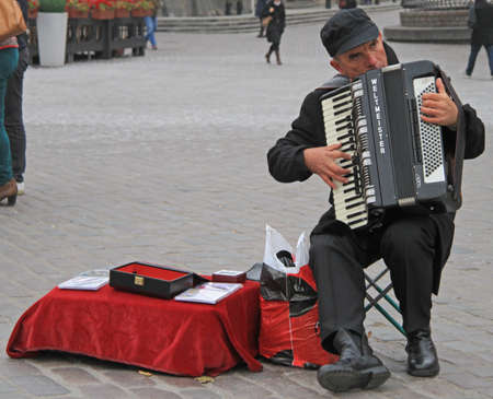 busker: Warsaw, Poland - October 25, 2015: man are playing the accordion at the square nearly Royal Castle in Warsaw
