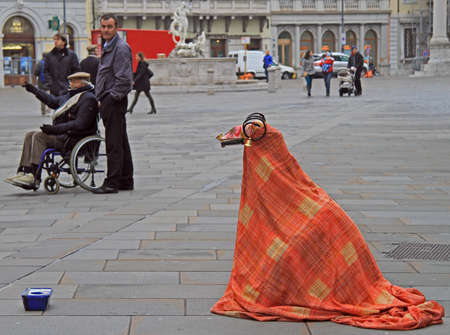 show bill: Trieste, Italy - November 20, 2015: street artist in the strange costume is entertaining passers nearly the central square in Trieste, Italy