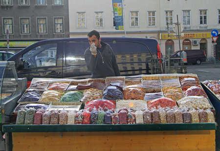 frutos secos: Viena, Austria - 10 de noviembre de 2015: el hombre es la venta de nueces y frutos secos en el mercado de la calle en Viena, Austria Editorial
