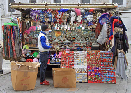 the merchant of venice: Venice, Italy - November 23, 2015: the black man is selling souvenirs and carnival masks outdoor in Venice, Italy